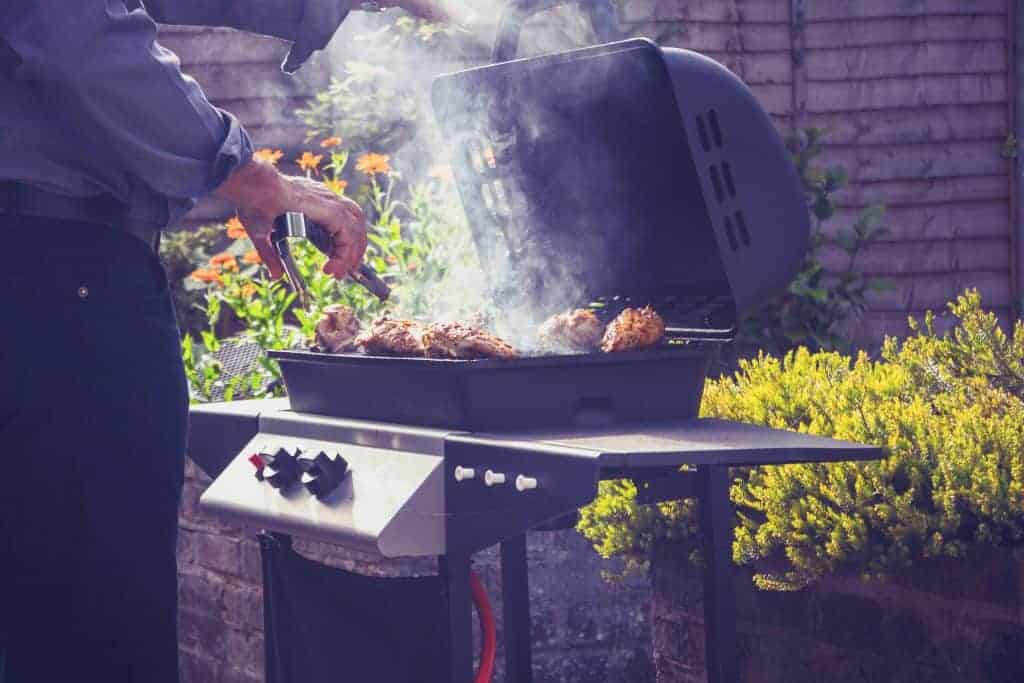 man barbecuing on gas grill